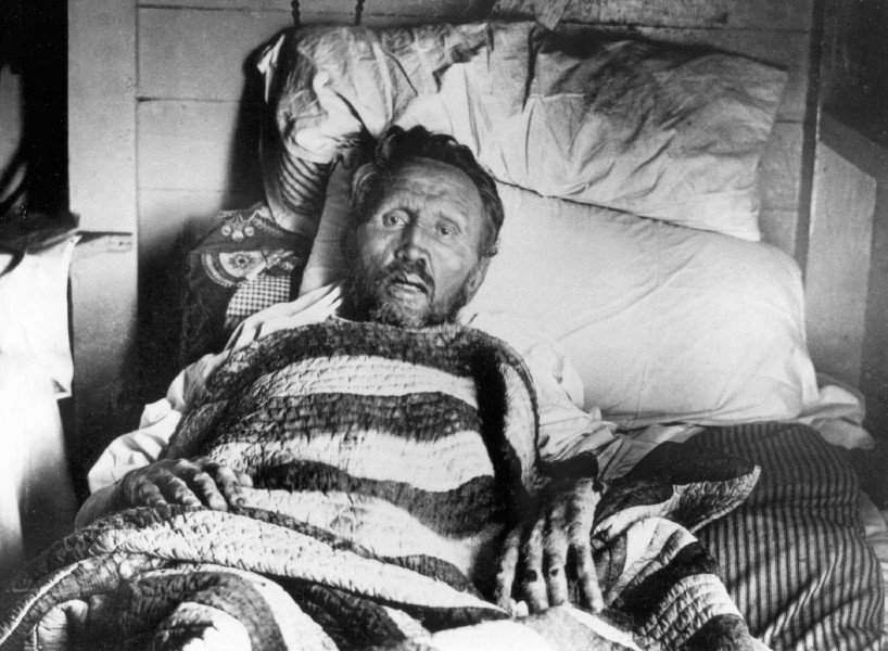 """Sydney B. Swift [Public domain], <a href=""""https://commons.wikimedia.org/wiki/File:Father_Damien_on_his_deathbed.jpg""""  target=""""_blank"""">via Wikimedia Commons</a>"""