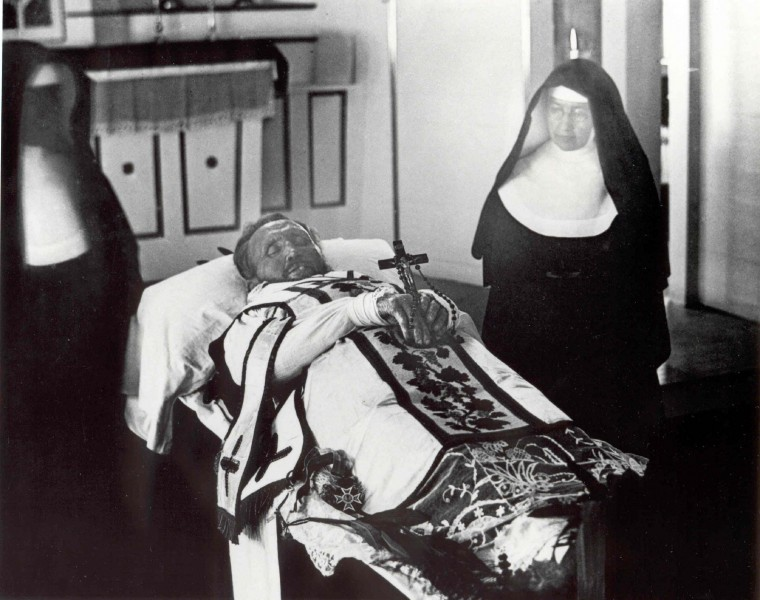 """Sydney B. Swift [Public domain], <a href=""""https://commons.wikimedia.org/wiki/File:Father_Damien_on_his_funeral_bier_with_Mother_Marianne_Cope_by_his_side.jpg""""  target=""""_blank"""">via Wikimedia Commons</a>"""