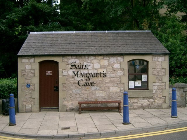 """Paul McIlroy&nbsp;/&nbsp;<i>St Margaret's Cave</i>, <a href=""""https://commons.wikimedia.org/wiki/File:St_Margaret%27s_Cave_-_geograph.org.uk_-_219483.jpg""""  target=""""_blank"""">via Wikimedia Commons</a><br /> <b>Description : </b><br /> <p>St Margaret's Cave. This small building which is situated in the Glen Bridge car park is the entrance to the cave which is named after Queen Margaret, who used to meditate and pray here in the 11th century. She was Queen of Scotland, canonised in 1250 and made patron saint of Scotland in 1673. The cave is one of Scotland's holiest shrines.  During the construction of the car park in 1969 the council wanted to bury the cave under tons of concrete. This sparked a public outcry and the council then agreed to build a tunnel under the car park to allow access to the cave. From this building 84 steps lead down to a tunnel which then turns into a single chamber 10 feet long by 8 feet wide and 8 feet high</p>"""